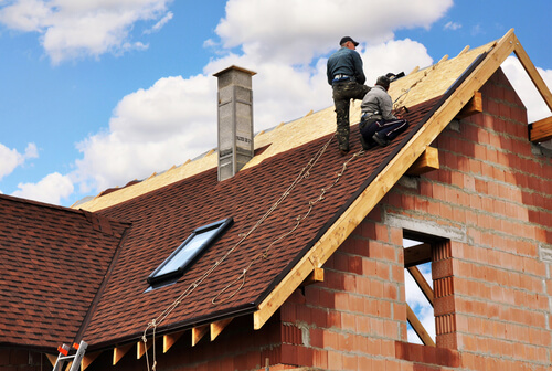 Two men tiling new roof on top of house