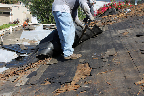 Man re-roofing house