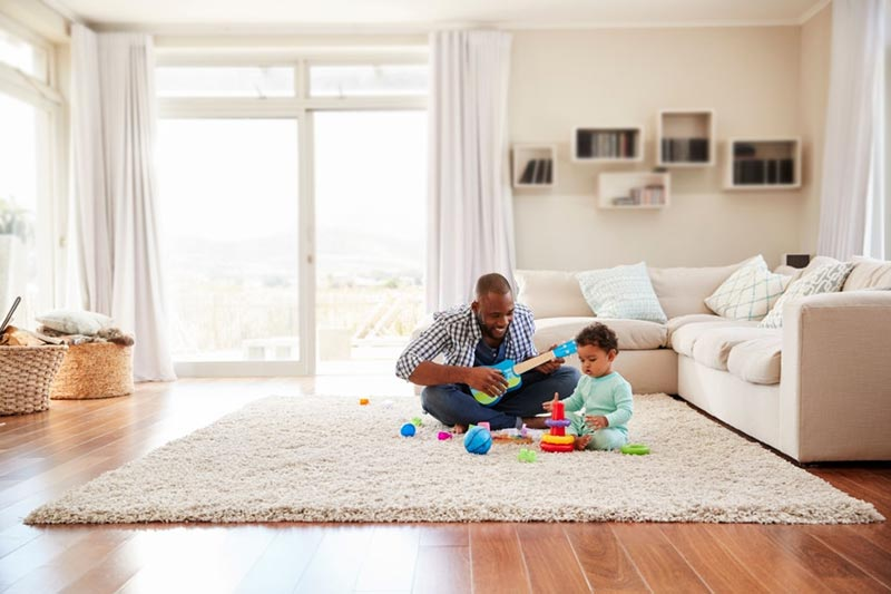 a black father and toddler playing in sitting room with area rug on wood floor