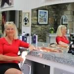Corinne Perron, assise à proximité du comptoir aux magnifiques lavabos en cuivre de son salon de coiffure.