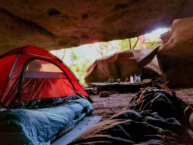 Campsite under a rock with a tent and sleeping bags
