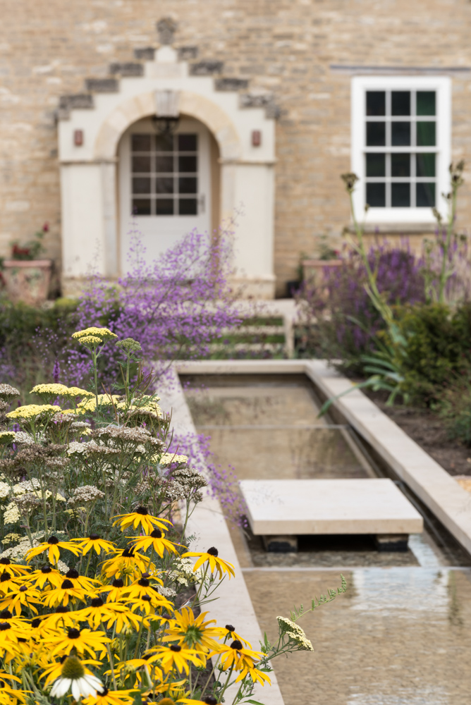 A rill with a stepping stone edged with Rudbeckia fulgida, Achillea, Echinacea and Thalictrum.