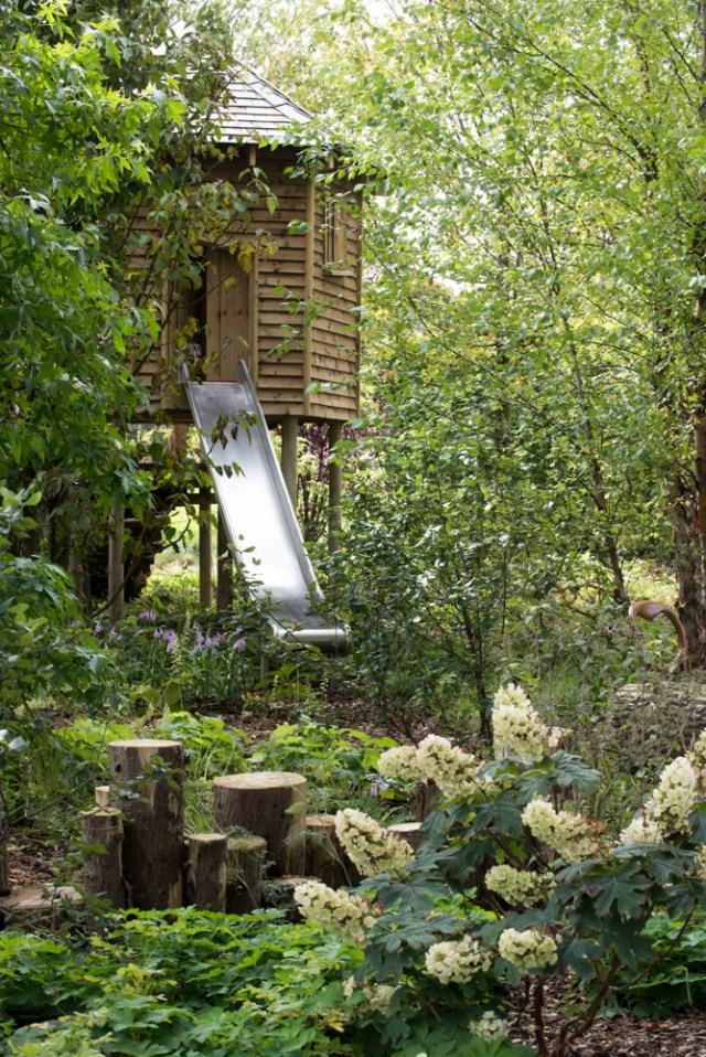 A tree house with a slide in the woods. Garden designed by: Anoushka Feiler