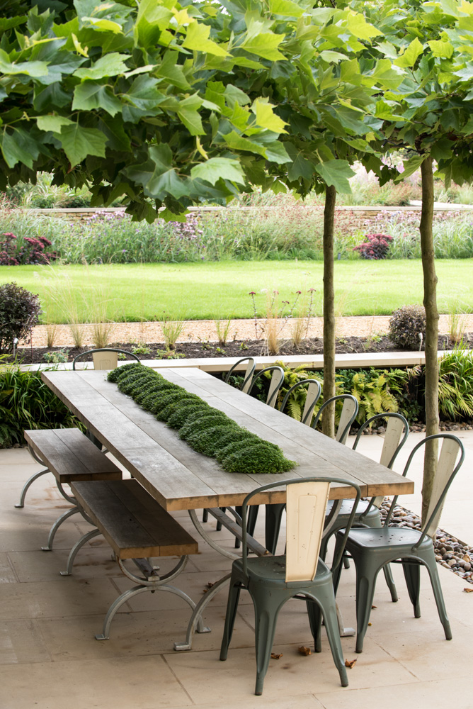 A garden table, with a ribbon of Mind Your Own Business down the centre, placed under a canopy of Plane leaves