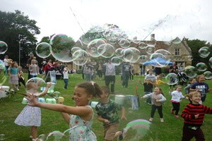 lots of small children chasing bubbles