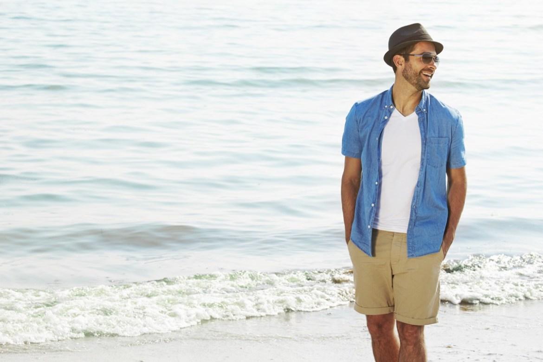 Man on the beach wearing bermuda shorts