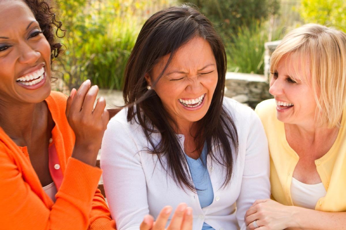 Tres mujeres de mediana edad riendo al aire libre, amiga