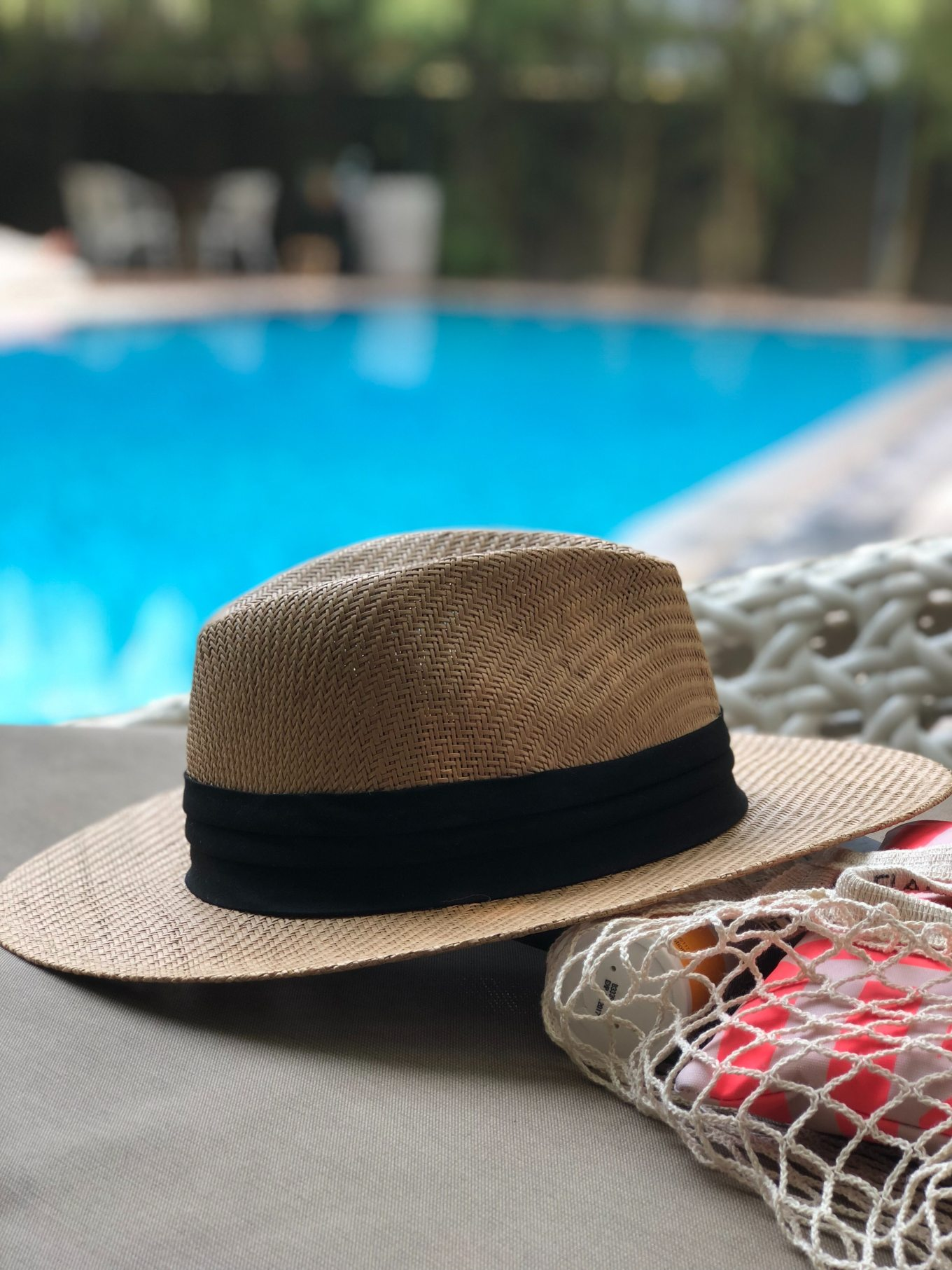 beige-and-black-hat-near-swimming-pool-984619