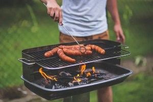 Man preparing sausages on a barbecue.