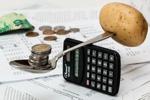 Spoon balancing on a calculator with coins and potato