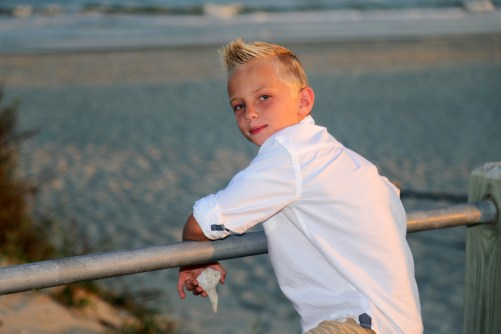 Boy on rail at the beach