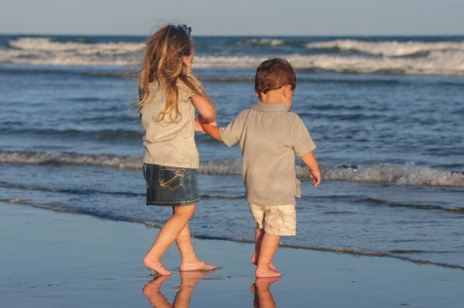 Little girl holding her brothers hand on the beach