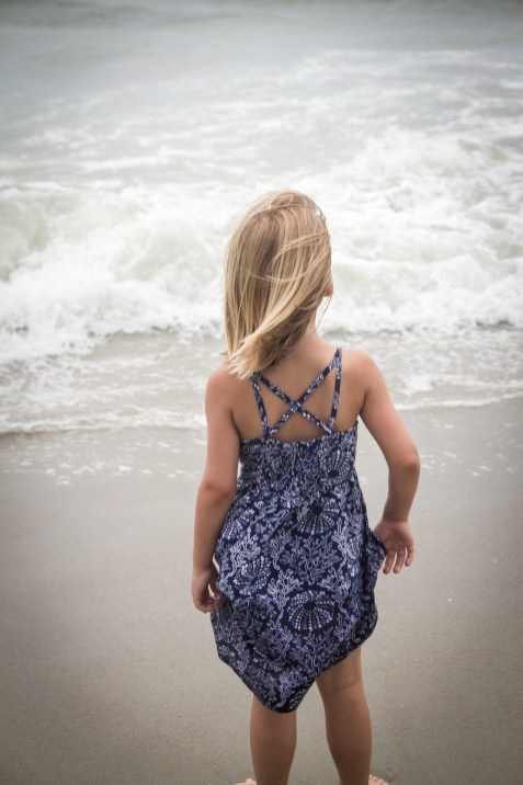 little girl looking out at ocean