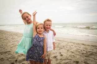 3 small children waving on the beach wearing multi colors