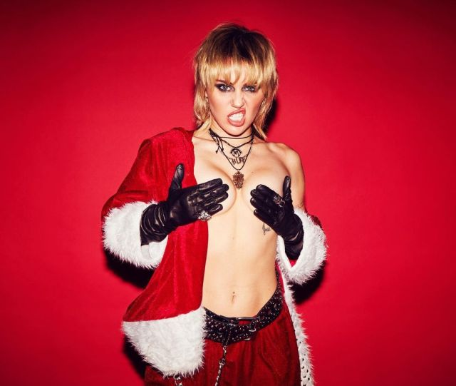 Miley Cyrus covering her breasts