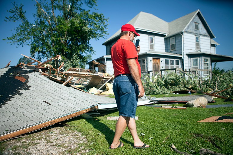 Doug Sage of Cameron uses the Skype app on his cell phone to display damage to his home to his daughter Courtney Sage, who is studying abroad in Korea. Sage's home and garage suffered extensive damage after a tornado swept through the village on Thursday, July 16, 2015. STEVE DAVIS/The Register-Mail
