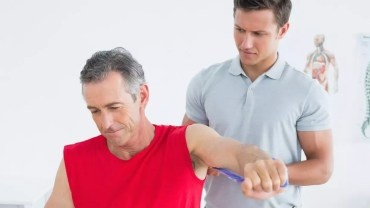 NJ Health-Male physiotherapist examining mans arm