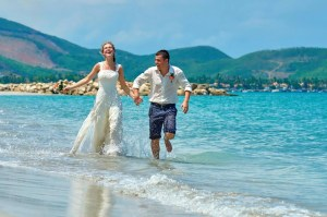 Happy Bride and groom running on a beautiful tropical sand beach.
