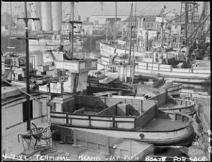 "Fishing boats, formerly operated by residents of Japanese ancestry, are tied up for the duration at Terminal Island in Los Angeles harbor. Note the ""For Sale"" signs. Evacuees of Japanese ancestry were housed in War Relocation Authority centers for the duration."