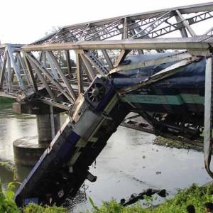 Assam: A passenger train hangs from a bridge after it derailed at Basugaon near Kokrajhar -Chirang district border of Assam on May 23, 2015. (Photo: IANS)