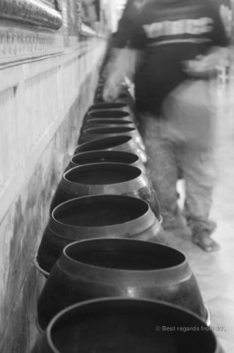 Dropping coins in the 108 bronze bawls as offerings to the reclining Buddha for good fortune, Wat Pho, Bangkok