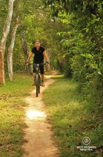Mountain biking the circular trail around the moat of Angkor Thom, Angkor, Cambodia