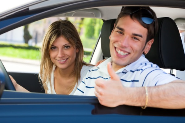 young couple in car showing thumbs up