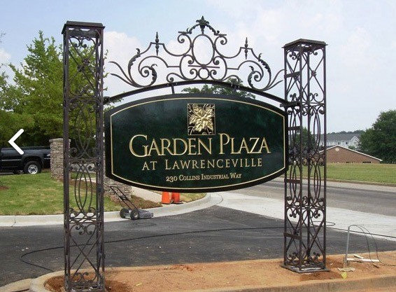 Garden Plaza - Sign made from a metal bed frame.