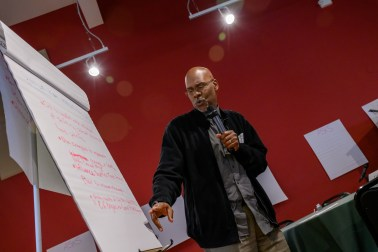 Photo description: Rainier Beach Action Coalition co-founder and Managing Strategist, Gregory Davis speaks into a microphone while pointing to writing on a flipchart, behind him is a red wall with flipchart postings on it.
