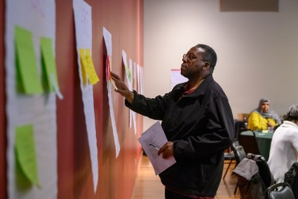 A Black man, wearing a black jacket, looks at a post it note on a sheet of paper taped to a red wall alongside several other sheets of paper; out of focus individuals sit at tables in the background.