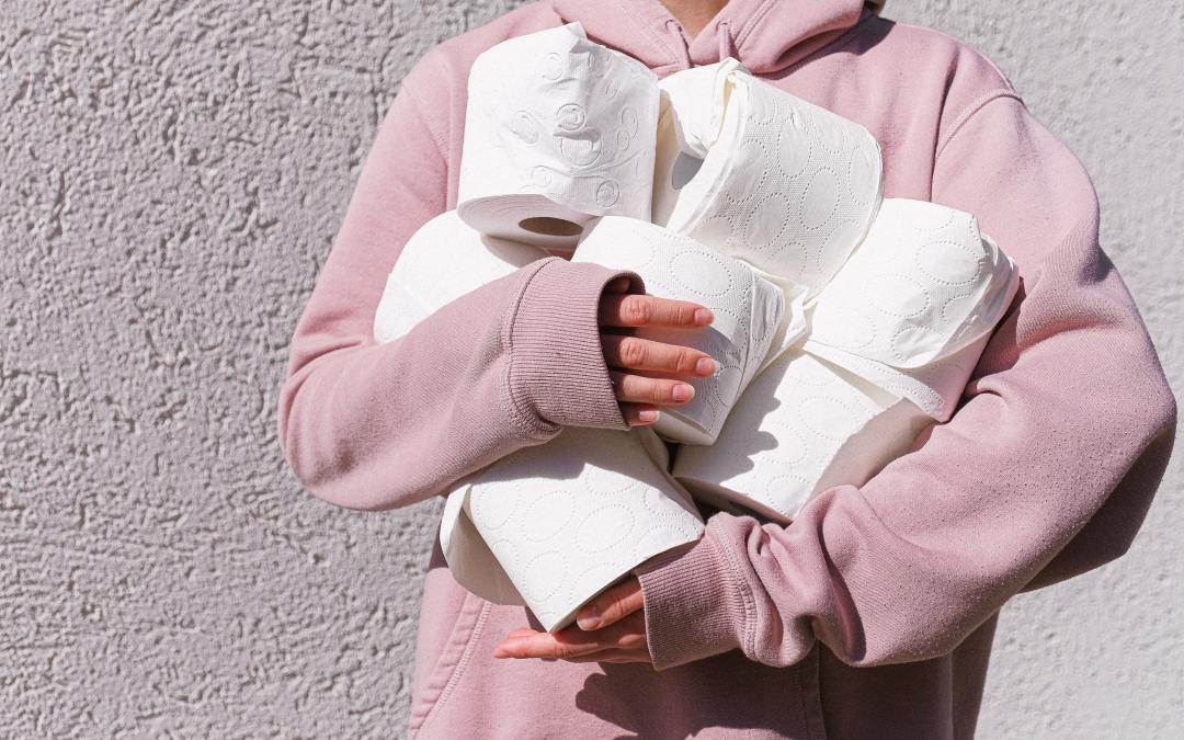 woman in pink sweater holding toilet rolls
