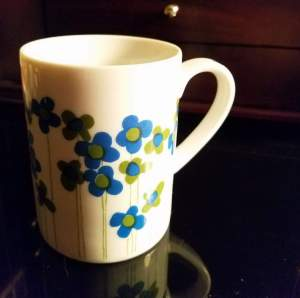 White vintage mug with blue and green flowers