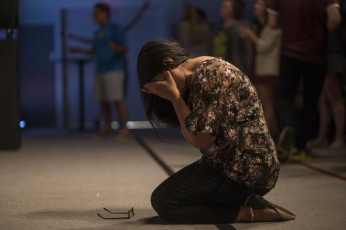 [Woman praying on her knees]