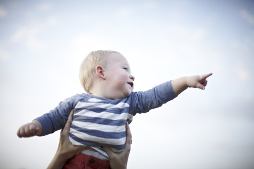 A toddler points off into the distance.