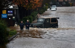 Residences near the Novato RV Park wades through standing water along Armstrong Ave. on Sunday, Jan. 8, 2017, in Novato, Calif. Residences were advised to shelter in place.(Robert Tong/Marin Independent Journal)