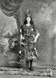 new-zealand-circa-1910-studio-portrait-young-woman-in-christmas-tree-fancy-dress-and-hat-costume-with-little-presents-and-decorations-hanging-off-her-christchurch-half-plate-glass-negative-by-adam-m