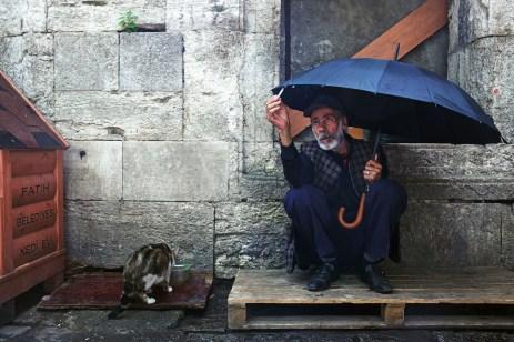 turkey_istanbul_fatih_man_umbrella_cat_cigarette_street_photography