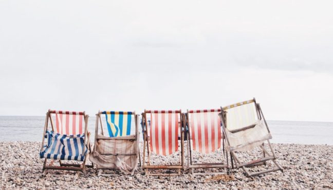 Women's group symbolized by happy, imperfect chairs on a sandy beach