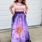 Purple Maxi Gathered Waist with a giant pink flower worn with a tshirt that says Be Kind and a big brimmed sun hat
