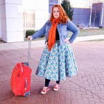 Beth Smith dressed for travel in a denim jacket, tea length floral skirt, orange scarf and red sneakers