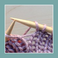 Between two knit stitches.