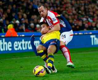 Stoke City's Charlie Adam (top) gets a yellow card for this foul on Arsenal's Alexis Sanchez during their English Premier League soccer match in Stoke, northern England December 6, 2014. REUTERS/Eddie Keogh (BRITAIN - Tags: SOCCER SPORT) EDITORIAL USE ONLY. NO USE WITH UNAUTHORIZED AUDIO, VIDEO, DATA, FIXTURE LISTS, CLUB/LEAGUE LOGOS OR 'LIVE' SERVICES. ONLINE IN-MATCH USE LIMITED TO 45 IMAGES, NO VIDEO EMULATION. NO USE IN BETTING, GAMES OR SINGLE CLUB/LEAGUE/PLAYER PUBLICATIONS.FOR EDITORIAL USE ONLY. NOT FOR SALE FOR MARKETING OR ADVERTISING CAMPAIGNS
