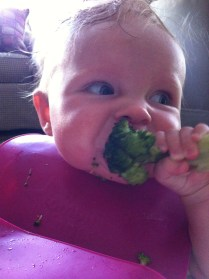 her very first big-girl food, steamed brocolli