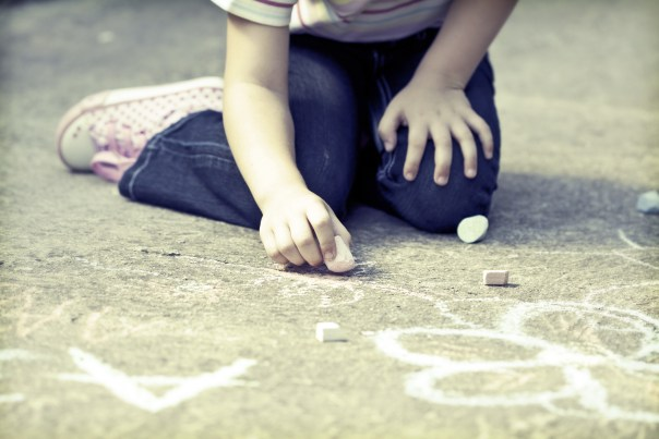 Photo of girl writing with chalk on the schoolyard