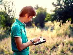 Young guy with a tablet outdoors teal