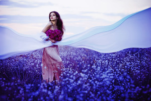 Beautiful woman in the sunset field