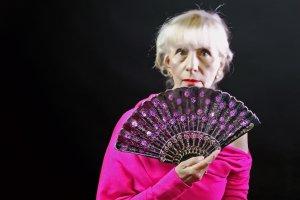 Senior Adult Female Showing Her Face Over Her Ornate Fan