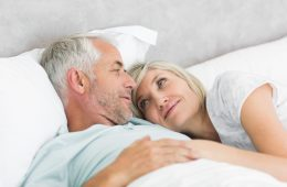 Loving mature couple lying in bed