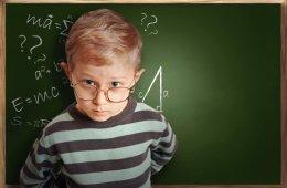 Clever pupil boy in eyeglasses near schoolboard