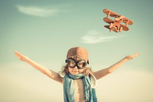 Happy kid playing with toy airplane